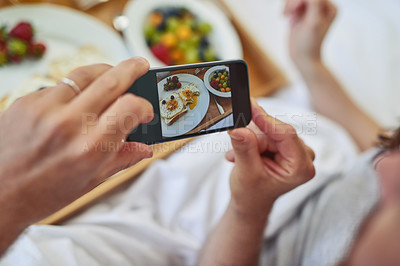 Buy stock photo PoV shot of an unrecognizable couple taking a photo of their breakfast that they're having in bed during morning hours