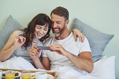 Buy stock photo Shot of a cheerful young couple sitting in bed while enjoying breakfast together and taking a picture during morning hours