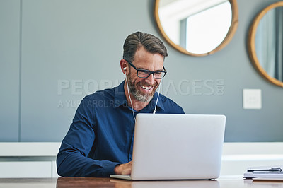 Buy stock photo Shot of a cheerful middle aged businessman making a Skype call on his laptop at home during the day