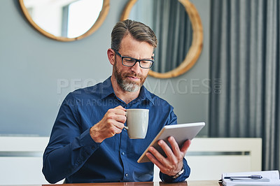Buy stock photo Shot of a focused middle aged businessman browsing on a digital tablet while enjoying a cup of coffee at home during the day