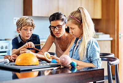 Buy stock photo Shot of a mother helping her two young children with a school project at home
