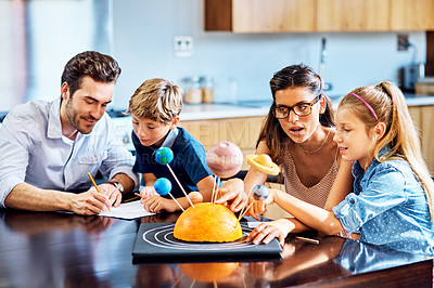 Buy stock photo Shot of parents helping their kids with a school project at home