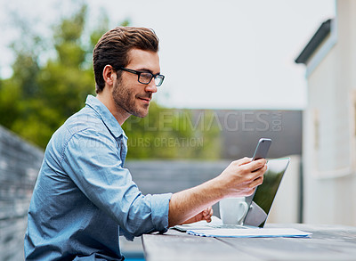 Buy stock photo Shot of a handsome young man using a laptop and cellphone outdoors