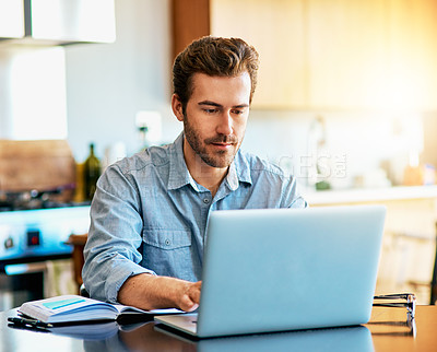 Buy stock photo Shot of a handsome young man working on a laptop at home