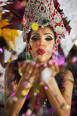 Buy stock photo Shot of a samba dancer blowing confetti from her hands while performing in a carnival