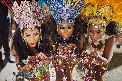 Buy stock photo Shot of samba dancers blowing confetti from their hands while performing in a carnival