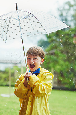 Buy stock photo Portrait of a cheerful little boy standing with an umbrella outside on a rainy day