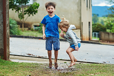 Buy stock photo Portrait of two cheerful young children jumping around in mud outside during a rainy day