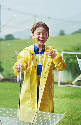 Buy stock photo Shot of a cheerful little boy standing with an umbrella while getting soaked with rain outside during the day