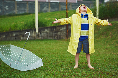 Buy stock photo Shot of a cheerful little boy standing with an umbrella while opening his mouth to catch rain drops outside on a rainy day