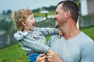 Buy stock photo Shot of a cheerful little girl being held by her father while they look at each other's eyes outside during a rainy day
