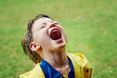 Buy stock photo Shot of a cheerful little boy standing on his own while opening his mouth to catch rain drops outside on a rainy day