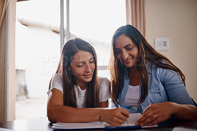 Buy stock photo Cropped shot of an attractive mother helping her daughter with her homework