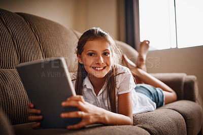 Buy stock photo Full length portrait of a young girl using her tablet while lying on a sofa at home
