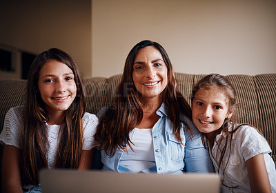 Buy stock photo Cropped portrait of an attractive mother watching movies on a laptop with her two daughters at home