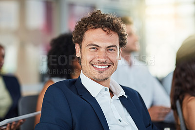 Buy stock photo Cropped portrait of a handsome young businessman attending a seminar with his colleagues