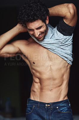 Buy stock photo Cropped shot of a handsome young man undressing at home