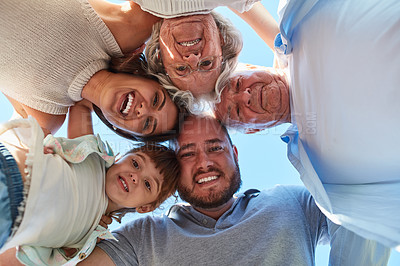 Buy stock photo Low angle portrait of a happy three generation family huddled together outdoors