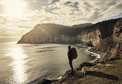 Buy stock photo Rearview shot of a handsome young man taking in the sights while hiking in the mountains