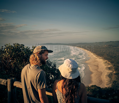 Buy stock photo Shot of a young couple admiring the scenic view along the coast