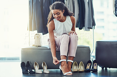 Buy stock photo Shot of an attractive young woman trying on shoes while on a shopping spree in a boutique
