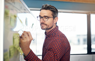 Buy stock photo Shot of a mature businessman writing on a whiteboard in an office