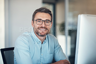 Buy stock photo Shot of a handsome mature businessman using a computer at his desk in a modern office