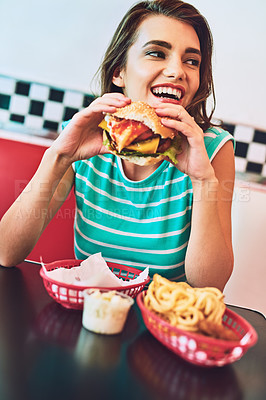 Buy stock photo Cropped shot of an attractive young woman enjoying a burger in a retro diner