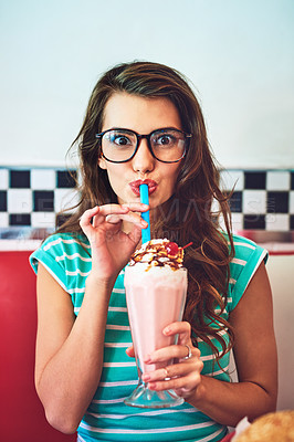 Buy stock photo Cropped portrait of an attractive young woman enjoying a milkshake in a retro diner
