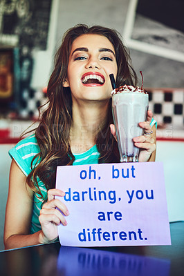 Buy stock photo Cropped shot of an attractive young woman holding up a sign while enjoying a milkshake in a retro diner