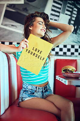 Buy stock photo Cropped shot of an attractive young woman holding up a sign in a retro diner