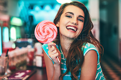Buy stock photo Cropped portrait of an attractive young woman eating a giant lollipop in a retro diner