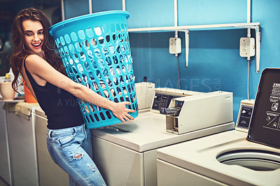 Buy stock photo Shot of an attractive young woman holding a basket of washing while standing inside of a laundry room during the day