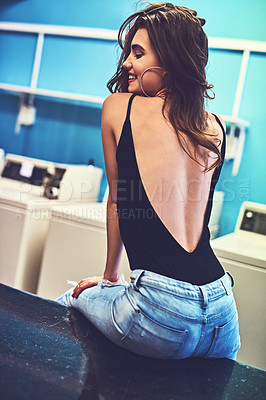Buy stock photo Rearview shot of an attractive young woman seated on a counter while waiting for her washing to wash inside of a laundry room during the day