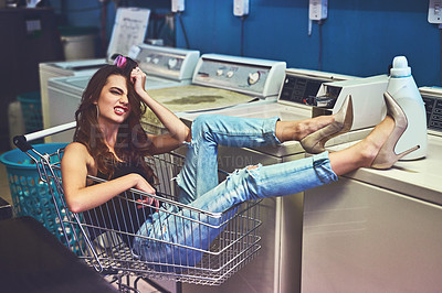 Buy stock photo Portrait of a attractive young woman seated inside of a shopping cart while resting her legs on a washing machine inside of a laundry room