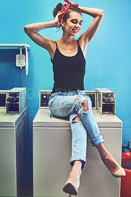 Buy stock photo Shot of an attractive young woman seated on a washing machine while holding her hair up and waiting for the washing to be done inside of a laundry room
