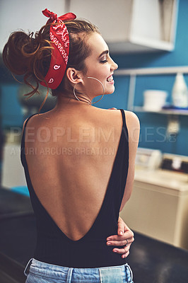 Buy stock photo Rearview shot of an attractive young woman standing inside of a laundry room to do washing while holding the sides of her waist