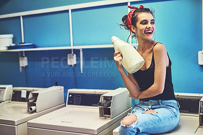 Buy stock photo Shot of an attractive young woman seated on a washing machine while holding bleach to wash her washing with inside of a laundry room during the day