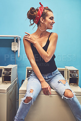 Buy stock photo Shot of an attractive young woman seated on a washing machine while waiting for the washing to be washed inside of a laundry room