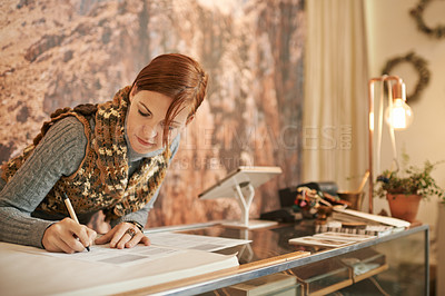 Buy stock photo Shot of a middle aged woman going through paperwork while working in a store