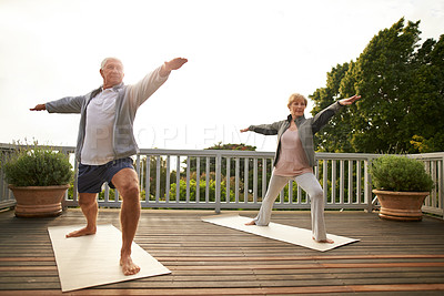 Buy stock photo Shot of a senior married couple practicing yoga at home