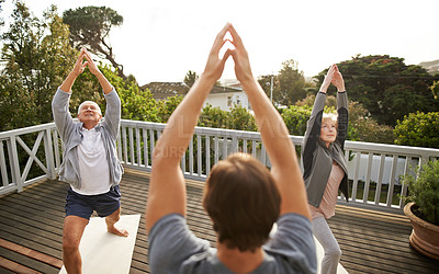 Buy stock photo Shot of a senior married couple  practicing yoga with a male instructor at home