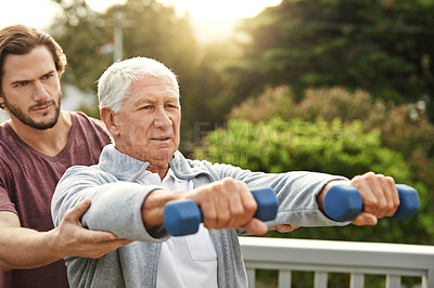 Buy stock photo Cropped shot of a senior man working out with a male instructor at home