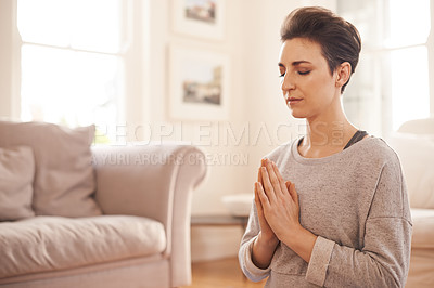 Buy stock photo Cropped shot of an attractive young woman practicing yoga in the living room at home
