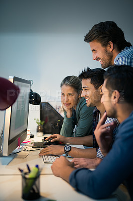 Buy stock photo Shot of a group of designers working together on a computer in an office