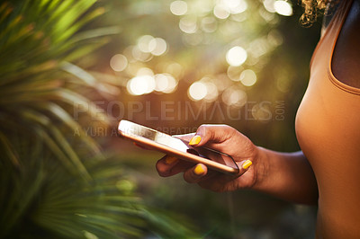 Buy stock photo Cropped shot of an unrecognizable woman using a cellphone in nature