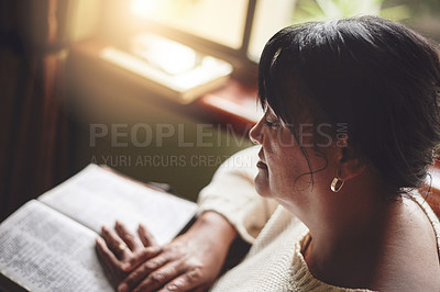 Buy stock photo Shot of a mature woman reading the Bible at home