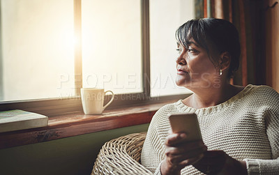 Buy stock photo Shot of a mature woman using a cellphone at home