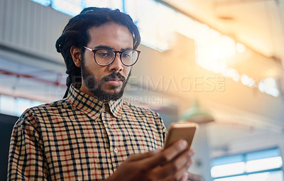 Buy stock photo Cropped shot of a handsome young male designer sending a text while standing in his office