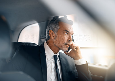 Buy stock photo Cropped shot of a handsome mature businessman making a call from the backseat of a car during his morning commute